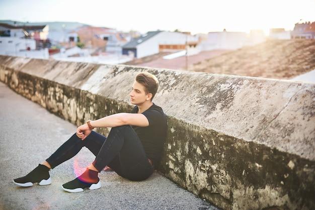 Hombre joven guapo en negro posando en la calle