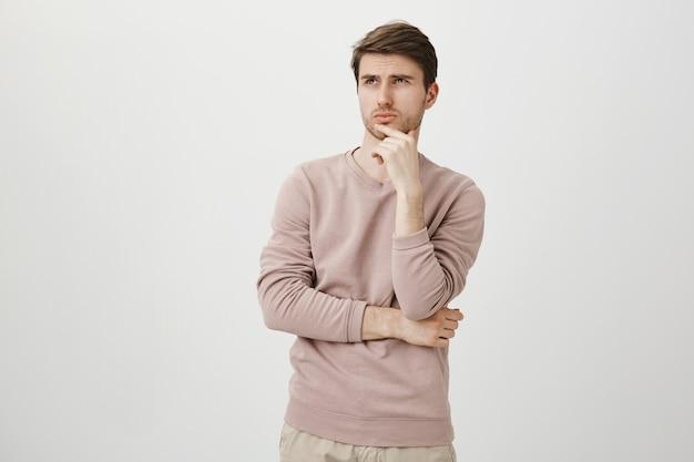 Hombre joven guapo pensativo haciendo una elección, mira la esquina superior izquierda en la promoción, pensando