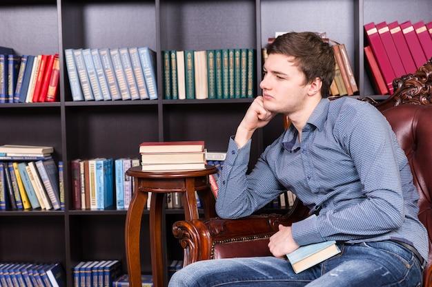 Hombre joven guapo pensativo sentado en la silla de la biblioteca mientras se apoya en su brazo y mira hacia la izquierda del marco.