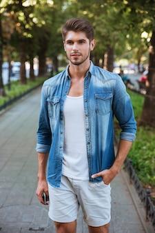 Hombre joven guapo de pie en la calle