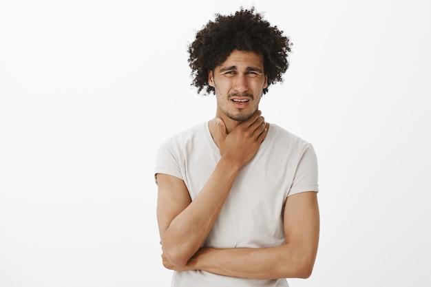 Hombre joven guapo quejándose de dolor de garganta, se enfermó