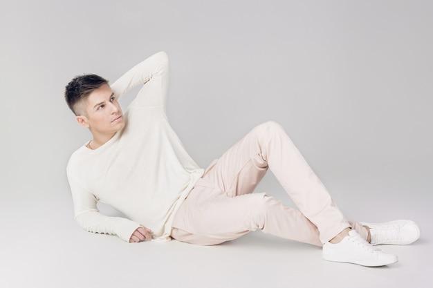 Hombre joven guapo con un suéter blanco y pantalones