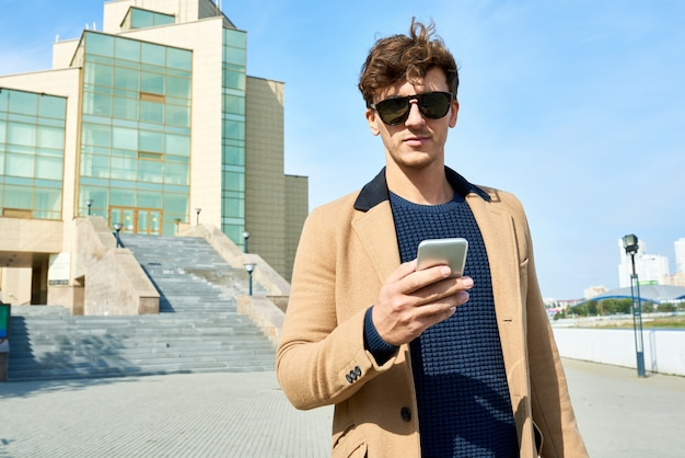 Hombre joven guapo con teléfono inteligente en calles de la ciudad