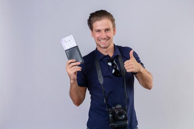 Hombre joven guapo viajero con cámara sosteniendo boletos de avión mirando a cámara con sonrisa en la cara feliz y positivo mostrando los pulgares para arriba sobre fondo blanco