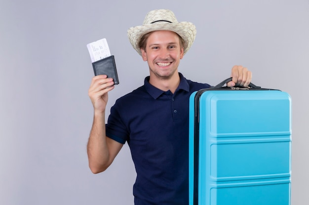 Hombre joven guapo viajero con sombrero de verano de pie con maleta sosteniendo boletos de avión mirando a cámara con cara feliz sonriendo alegremente sobre fondo blanco