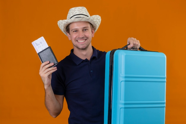 Hombre joven guapo viajero con sombrero de verano de pie con maleta sosteniendo boletos de avión mirando a cámara con cara feliz sonriendo alegremente sobre fondo naranja
