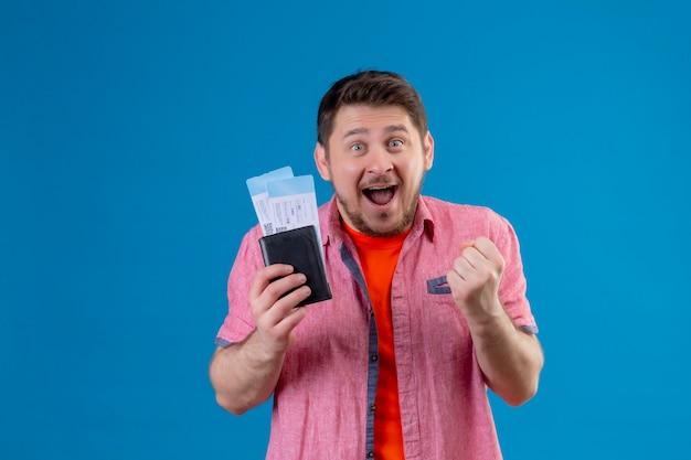 Hombre joven guapo viajero sosteniendo billetes de avión, apretando el puño regocijándose de su éxito