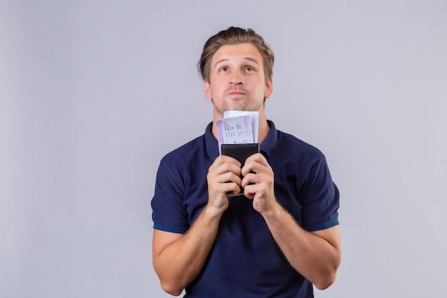 Hombre joven guapo viajero sosteniendo billetes de avión mirando hacia arriba con mirada soñadora de pie sobre fondo blanco.