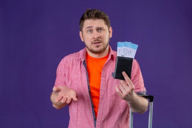 Hombre joven guapo viajero sosteniendo billetes de avión mirando confundido