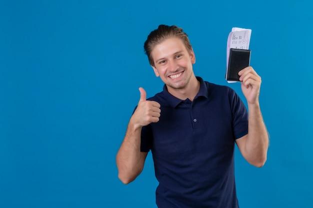 Hombre joven guapo viajero sosteniendo billetes de avión sonriendo alegremente con cara feliz mostrando los pulgares para arriba sobre fondo azul