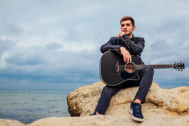 Hombre joven con guitarra acústica sentado en la playa rodeado de rocas en día lluvioso