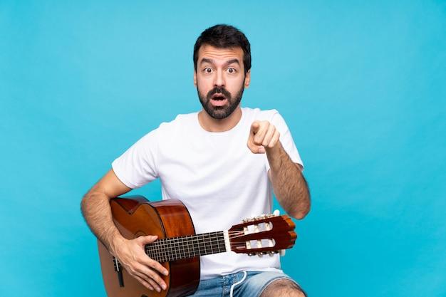 Hombre joven con guitarra sobre azul aislado sorprendido y apuntando al frente
