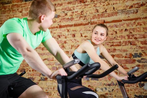 Hombre joven hablando con una linda rubia mientras ambos hacen algo de cardio en una bicicleta en el gimnasio