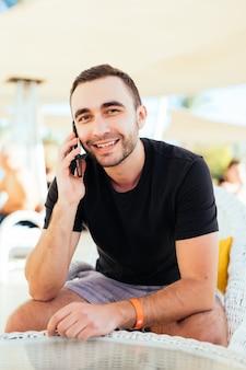 Hombre joven hablando con un teléfono inteligente en la terraza junto al mar. .