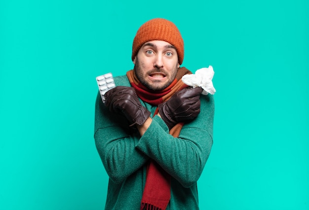 Hombre joven handome con tableta de píldoras. concepto de enfermedad, gripe o tos