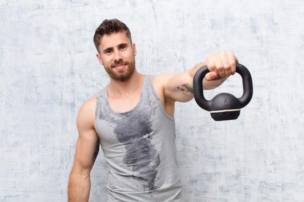 Hombre joven handosme contra la pared de color plano con un concepto de deporte con mancuernas