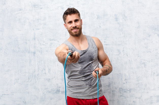 Hombre joven handosme contra la pared de color plano con una cuerda de saltar. concepto deportivo