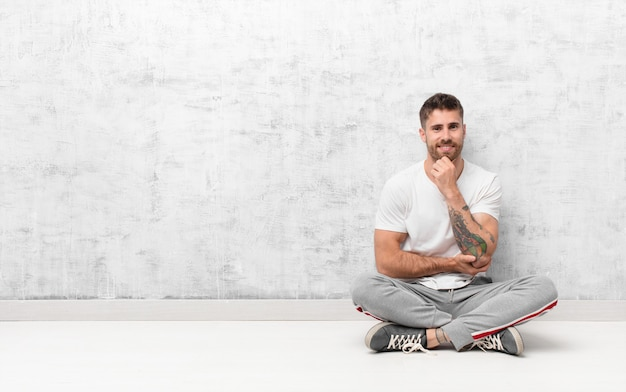 Hombre joven handosme que parece feliz y sonriente con la mano en la barbilla, preguntándose o haciendo una pregunta, comparando opciones con una pared de color plano