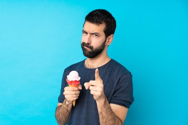 Hombre joven con un helado de cucurucho frustrado y apuntando hacia el frente