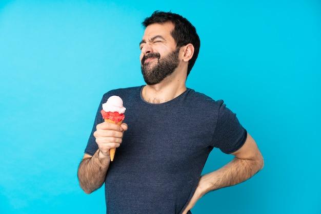 Hombre joven con un helado de cucurucho sobre la pared azul aislada que sufre de dolor de espalda por haber hecho un esfuerzo