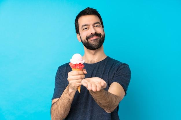 Hombre joven con un helado de cucurucho sobre pared azul aislado sosteniendo copyspace imaginario en la palma para insertar un anuncio