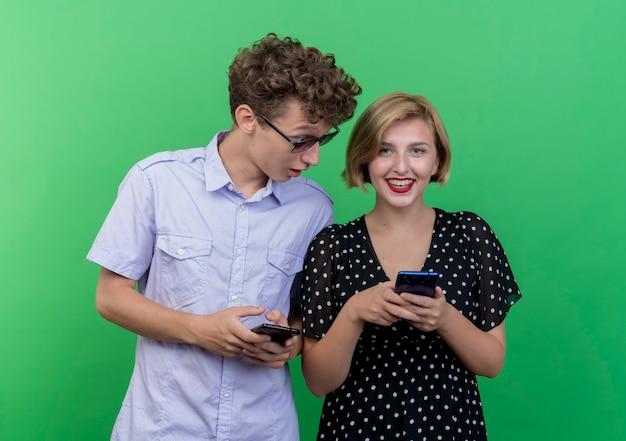 Hombre joven hermosa pareja espiando mirando el teléfono celular de su novia de pie sobre la pared verde