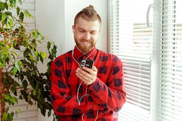 Hombre joven hermoso en los auriculares que sostienen el teléfono móvil