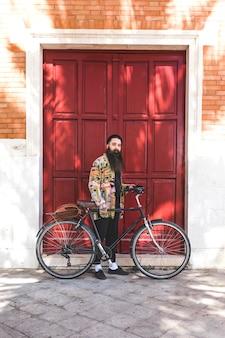 Hombre joven hermoso con la bicicleta que se coloca delante de la pared de madera de la puerta roja
