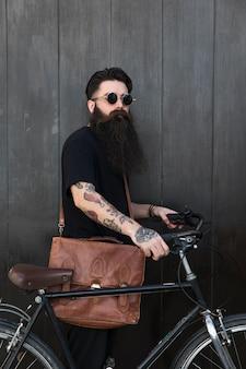 Hombre joven hermoso con la bicicleta que se coloca delante de la pared negra de madera