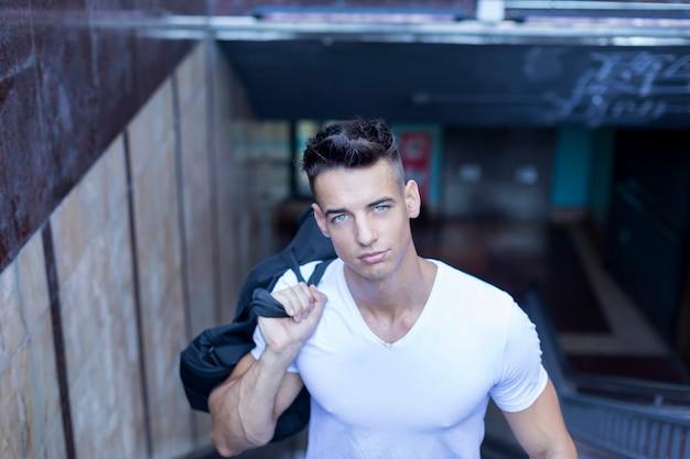 Hombre joven hermoso en el bolso que lleva de la camiseta blanca en hombro