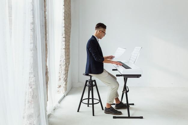 Hombre joven hermoso en la capa que mira la hoja musical que juega en el teclado