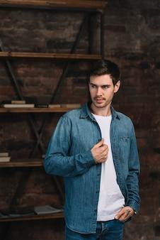 Hombre joven hermoso en la chaqueta del dril de algodón que mira lejos