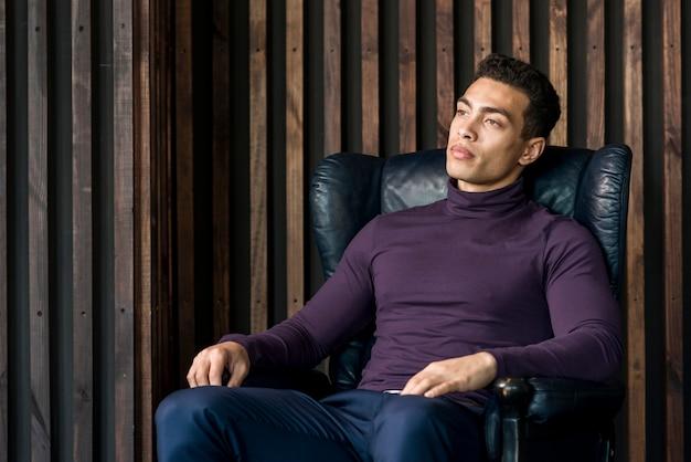 Hombre joven hermoso contemplado que se sienta en la butaca que mira lejos