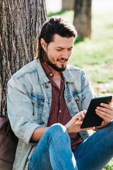 Hombre joven hermoso feliz que se sienta debajo del árbol usando smartphone