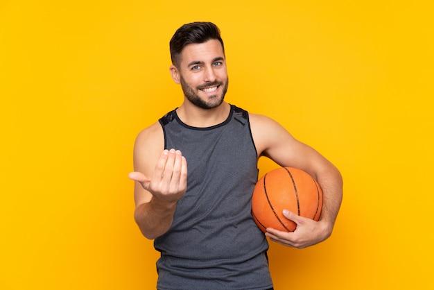 Hombre joven hermoso del jugador de básquet sobre la pared blanca aislada que invita a venir con la mano.