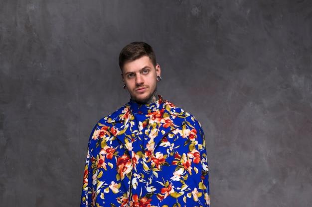 Hombre joven hermoso con la nariz y los oídos perforados que llevan la capa floral contra el contexto gris