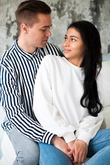Hombre joven hermoso que abraza a la mujer étnica bonita joven