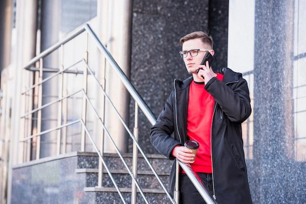 Hombre joven hermoso que se coloca en el monopatín en el teléfono móvil que sostiene la taza de café para llevar