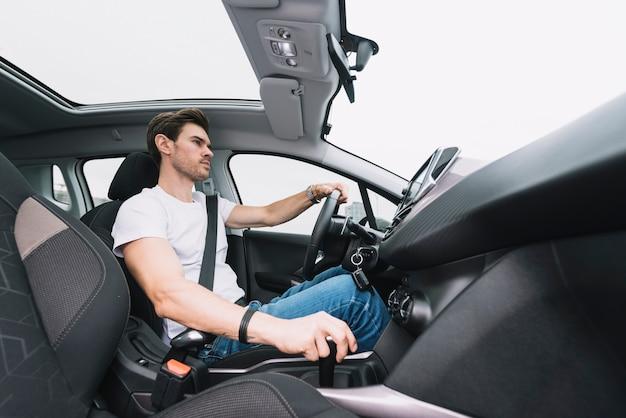 Hombre joven hermoso que conduce el coche moderno