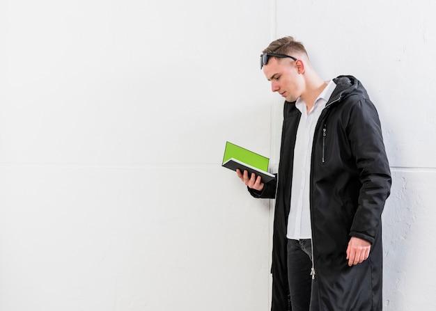 Hombre joven hermoso que lleva la chaqueta larga que lee el libro