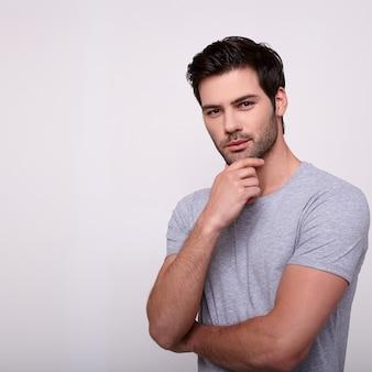 Hombre joven hermoso que mira la cámara y que guarda la mano en la barbilla.