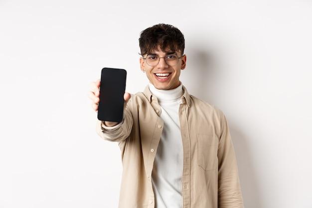 Hombre joven hermoso que muestra la pantalla vacía del teléfono inteligente, de pie sobre fondo blanco. copia espacio