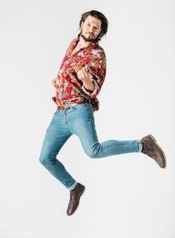 Hombre joven hermoso que salta en aire contra el fondo blanco