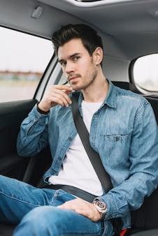 Hombre joven hermoso que se sienta en el asiento de carro que mira la cámara