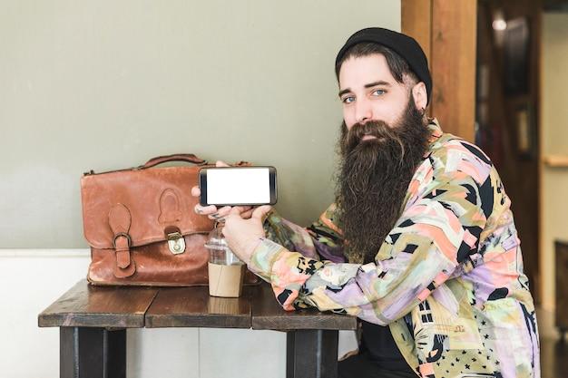 Hombre joven hermoso que se sienta en el café que muestra la pantalla del teléfono móvil