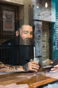 Hombre joven hermoso que se sienta en café usando el teléfono móvil