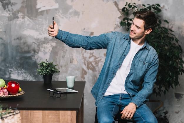 Hombre joven hermoso que se sienta en la cocina que toma el autorretrato a través del teléfono móvil