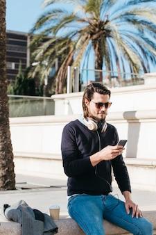 Hombre joven hermoso que se sienta en parque con la taza de papel del café usando el teléfono móvil