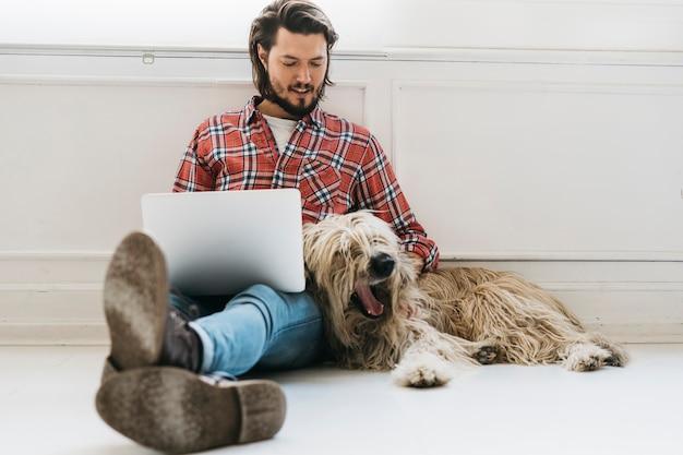 Hombre joven hermoso que se sienta en piso con el perro usando el ordenador portátil