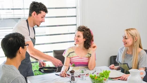 Hombre joven hermoso que sirve la verdura a sus amigos que se sientan en la mesa de comedor